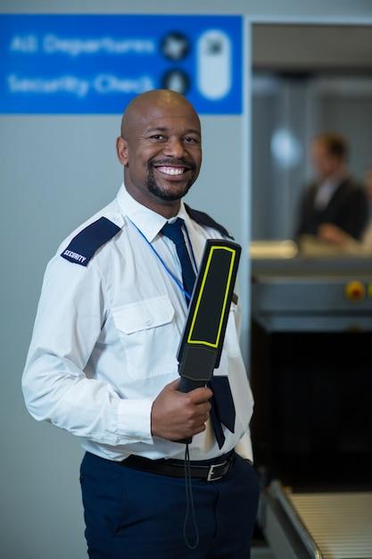 Agente de segurança do aeroporto sorridente segurando um detector de metais no terminal do aeroporto Foto gratuita