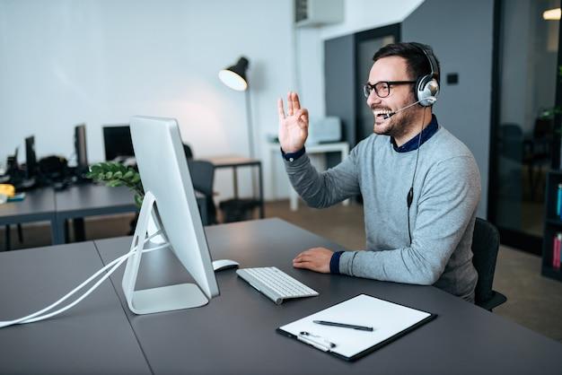 Agente de suporte técnico bonito falando com um cliente e dando-lhe o sinal de tudo bem. video chamada. Foto Premium