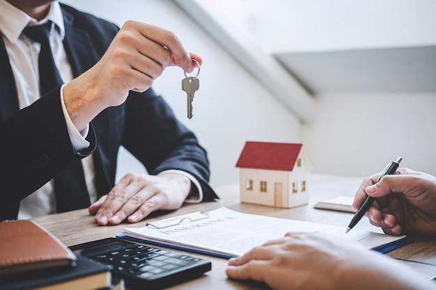Agente do corretor que dá as chaves da casa ao cliente após ter assinado a propriedade do contrato do acordo com aprovado Foto Premium