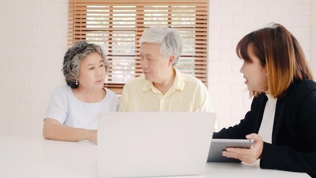 Agente feminina inteligente da ásia oferece seguro de saúde para casais idosos por documento, tablet e laptop. Foto gratuita