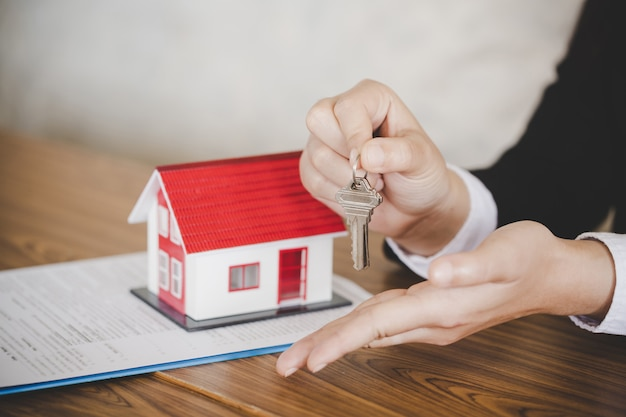 Agente imobiliário com modelo de casa e chaves Foto Premium
