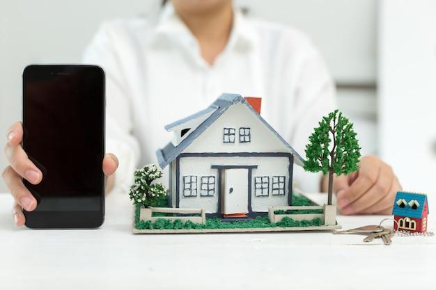 Agente imobiliário com modelo de casa e telefone Foto gratuita