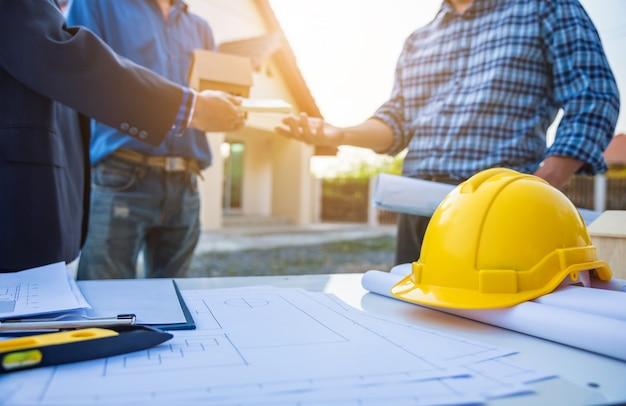 Agente imobiliário dando as chaves da casa na frente de casa ficar com arquiteto Foto Premium