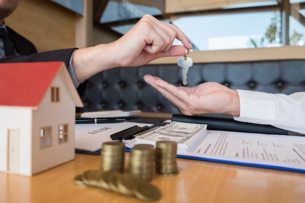 Agente imobiliário dando casa chave propriedade de acordo de sinal de cliente Foto Premium