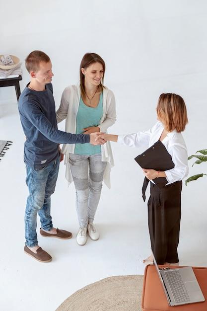 Agente imobiliário de alto ângulo fazendo um acordo Foto gratuita