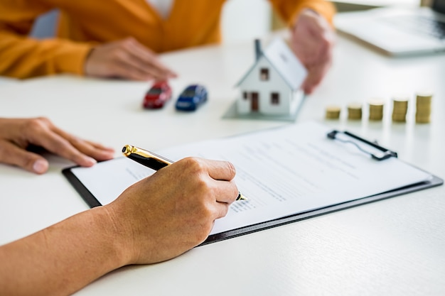 Agente imobiliário e cliente assinando contrato para comprar casa, seguro ou empréstimo imobiliário. Foto Premium