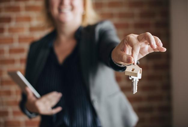 Agente imobiliário entregando as chaves Foto Premium