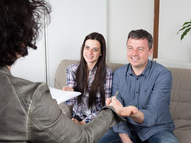Agente imobiliário entregar as chaves da casa para jovem casal Foto Premium