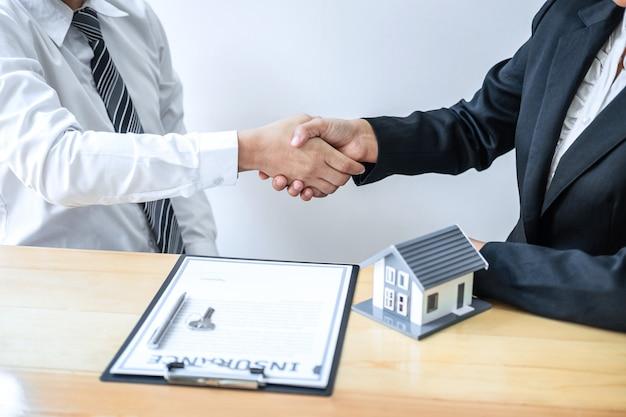 Agente imobiliário está apertando as mãos após um bom negócio e dando casa, chaves para o cliente depois de discutir e assinar contrato para comprar casa com o formulário de inscrição aprovado Foto Premium