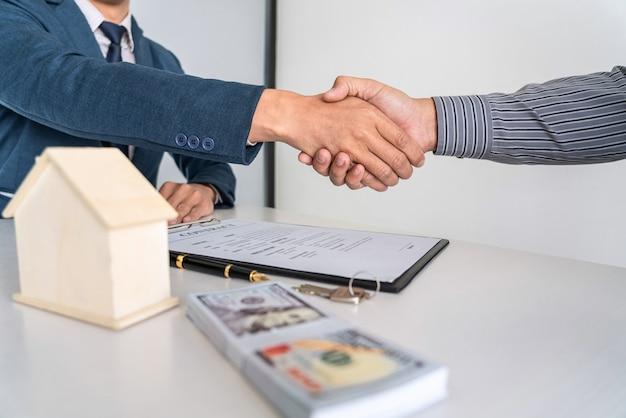 Agente imobiliário está apertando as mãos depois de um bom negócio e dando casa, chaves para o cliente depois de assinar contrato para comprar casa com formulário de pedido de propriedade aprovado Foto Premium