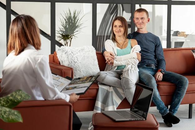 Agente imobiliário falando com casal Foto gratuita
