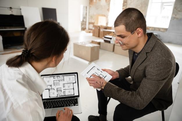 Agente imobiliário feminino mostrando a nova casa para um jovem depois de uma discussão sobre os planos da casa, movendo-se, novo conceito de casa Foto gratuita