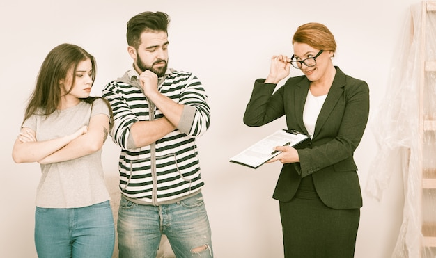Agente imobiliário mostra escrúpulos acordo para jovem casal em casa aberta Foto Premium