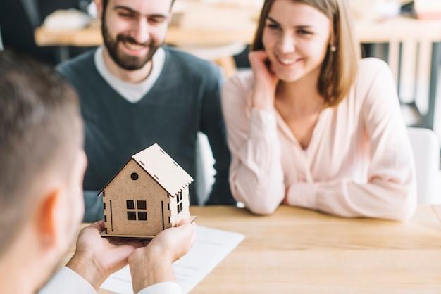 Agente imobiliário mostrando a casa de brinquedo para casal Foto gratuita
