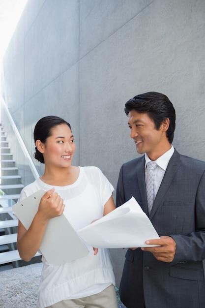 Agente imobiliário mostrando locação ao cliente e sorrindo Foto Premium