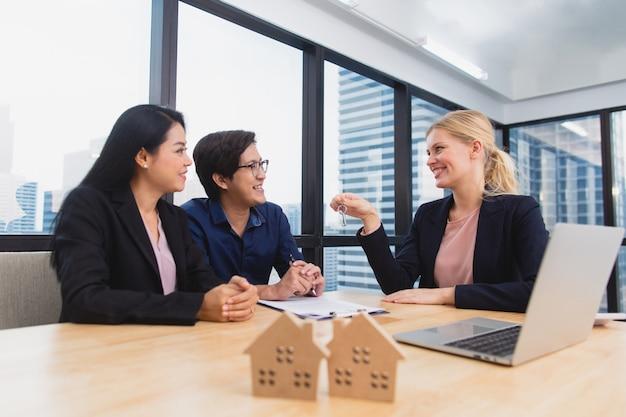 Agente imobiliário que encontra o par asiático para oferecer a propriedade de casa, o seguro de vida e o investimento da casa Foto Premium