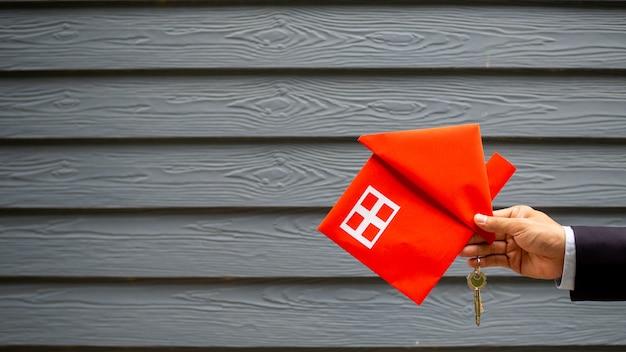 Agente imobiliário segurando a casa e a chave Foto Premium