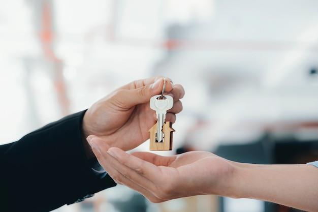 Agente imobiliário segurando a chave com chaveiro em forma de casa. Foto Premium