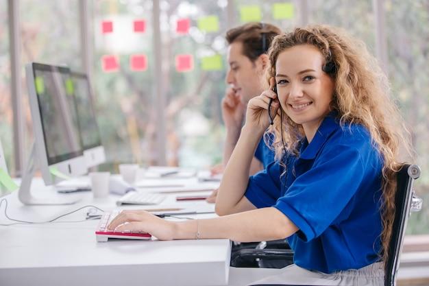 Agente jovem operador amigável com fones de ouvido trabalhando em um call center. Foto Premium