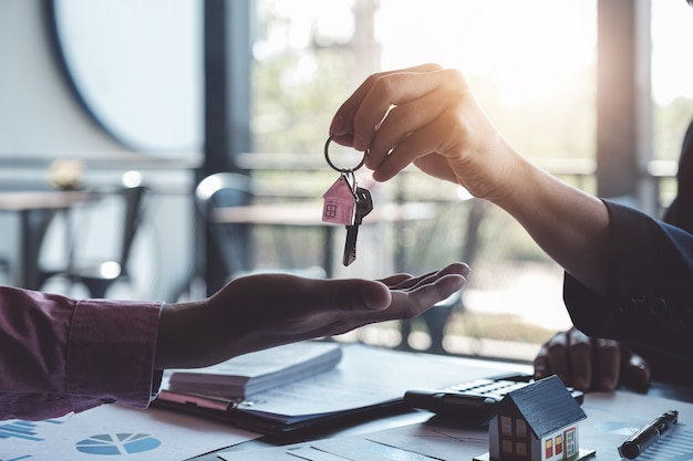 Agentes imobiliários concordam em comprar uma casa e dar chaves aos clientes nos escritórios da agência. Foto Premium