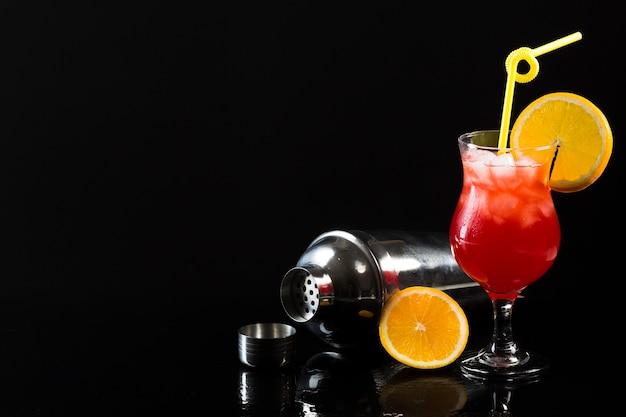 Agitador e copo de coquetel com espaço para texto e laranja Foto gratuita