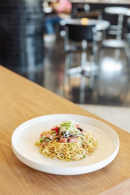Agite o macarronete chinês fritado com carne do presunto e de caranguejo na tabela de madeira com fundo do borrão. Foto Premium