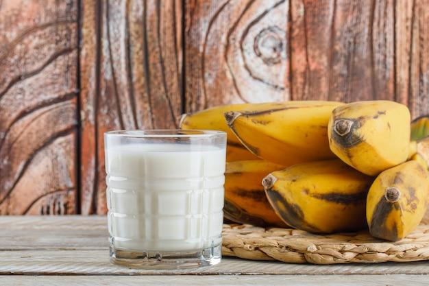 Aglomerado de bananas com vista lateral do leite em uma mesa de madeira e vime Foto gratuita