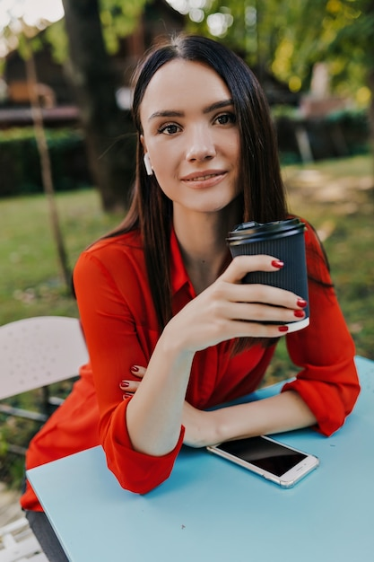 Agradável mulher morena de camisa vermelha se divertir no café de rua. Foto gratuita
