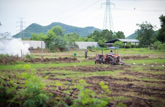 Agricultor em trator preparando terreno com cultivador de sementeira Foto Premium