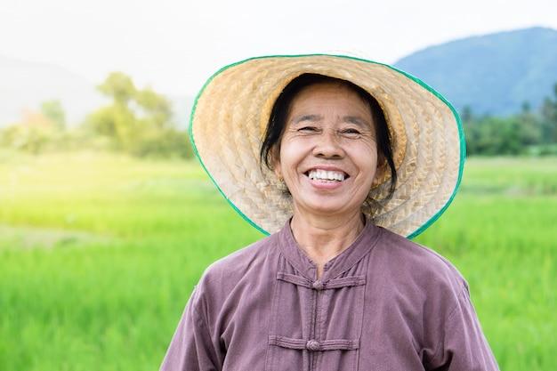 Agricultor feminino tailandês feliz sorrindo sobre fazenda de arroz verde |  Foto Premium