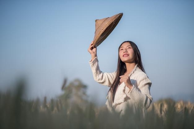 Agricultor feminino vietnamita colheita de trigo Foto gratuita
