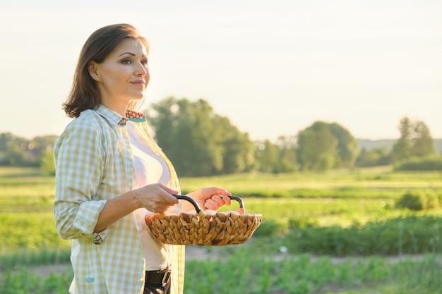 Agricultor maduro bonito da mulher com a cesta de ovos frescos Foto Premium