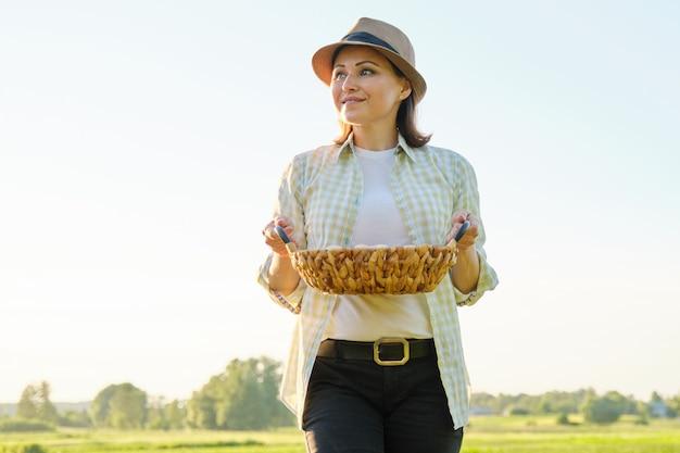 Agricultor maduro bonito da mulher com a cesta de ovos frescos, Foto Premium
