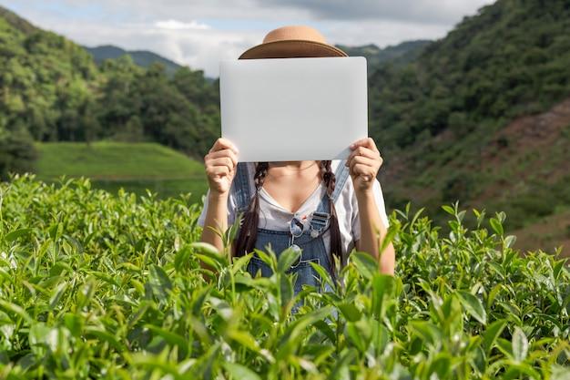 Agricultores segurando uma placa branca na plantação de chá Foto gratuita