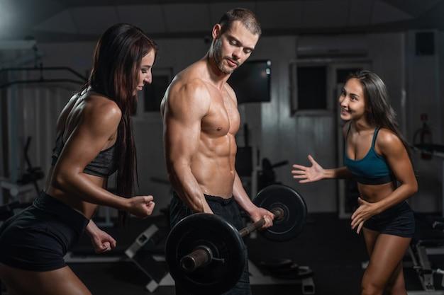 Agrupe com equipamento de treinamento do peso do dumbbell na ginástica do esporte. Foto Premium