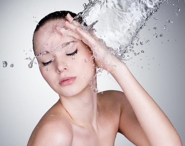 Água caindo no rosto de mulher linda sensualidade com pele limpa Foto gratuita