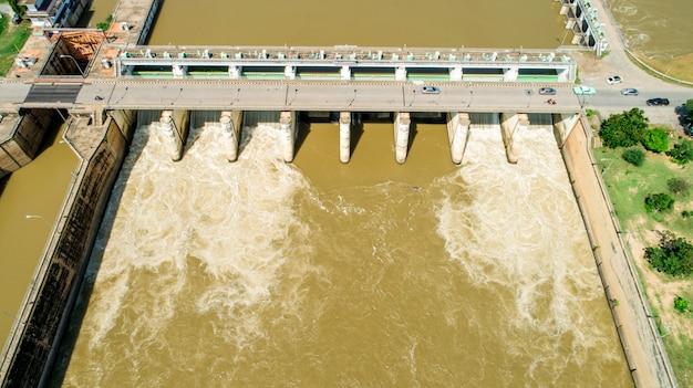 Água da inundação da mola do tiro aéreo que flui a represa da central eléctrica hidroeléctrica Foto Premium