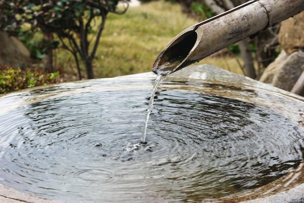 Água de bambu natural japonesa da tubulação que flui no lugar da lavagem. Foto Premium