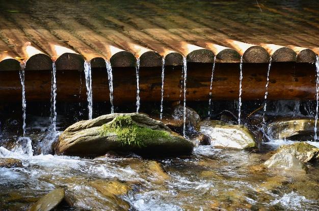 Água de madeira artesanal drena de pequenas vigas tratadas. um lindo fragmento de uma pequena cachoeira Foto Premium
