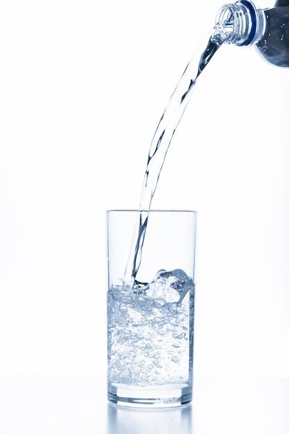 Água derramando em vidro isolado no fundo branco Foto Premium