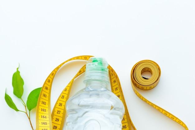Água engarrafada para vida saudável e fita métrica sobre um branco Foto Premium