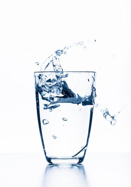 Água espirrando de vidro isolado no fundo branco Foto Premium