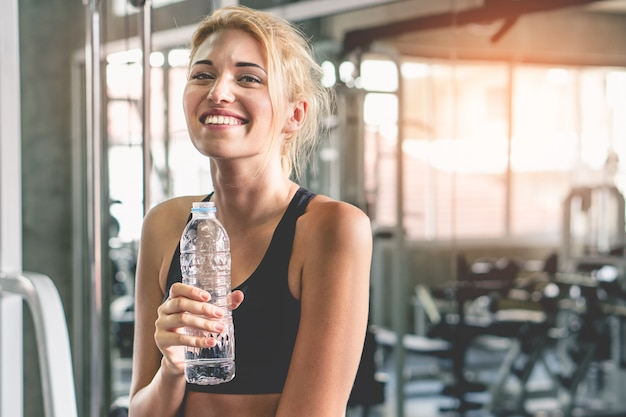 Água feliz da bebida da mulher do bem estar após o exercício no gym. Foto Premium