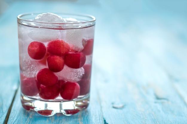 Água fria com gelo, cerejas e frutas. Foto Premium