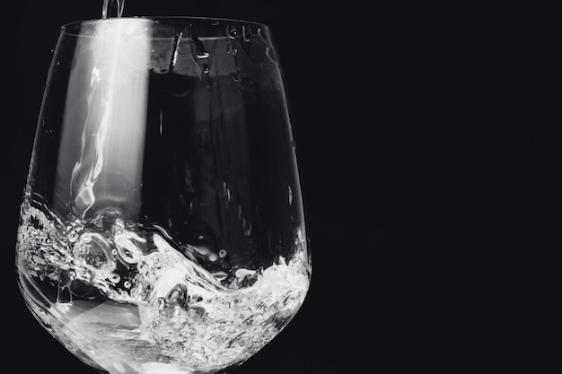 Água no copo isolado no preto Foto Premium