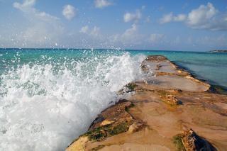 Água que quebra sobre uma barreira à beira-mar Foto gratuita