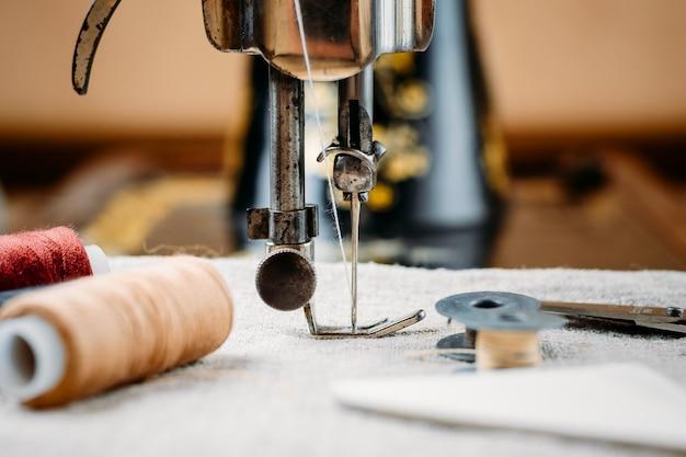 Agulha de aço com looper e um pé calcador de velho vintage mão máquina de costura close-up Foto Premium