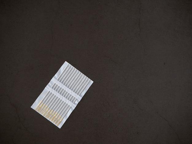 Agulha de costura em um fundo preto Foto Premium