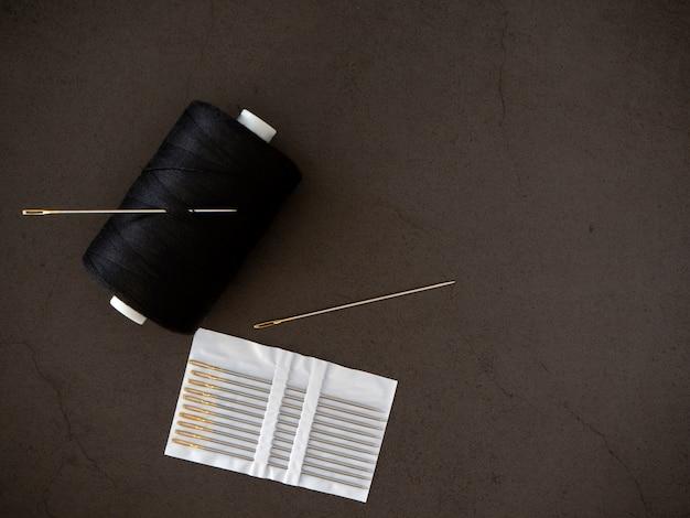 Agulha de linha em um fundo preto Foto Premium