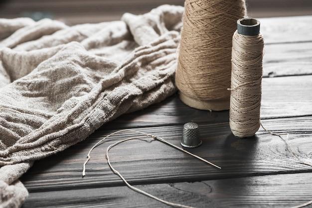 Agulha; piso de carretel e dedal com tecido de juta na mesa de madeira Foto gratuita
